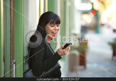 Woman Looking at Cellphone stock photo, Beautiful woman looking at her cellphone on a downtown street by Scott Griessel