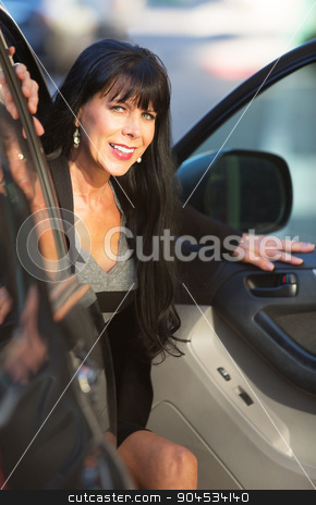 Beautiful Woman Exiting Vehicle stock photo, An attractive woman exits a vehicle on downtown street by Scott Griessel