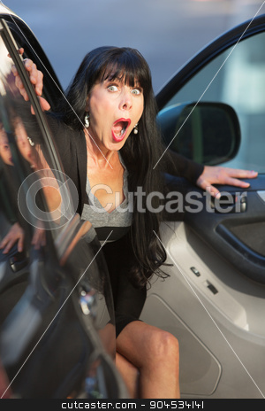 Surprised Woman Leaving a Car stock photo, A woman exits a vehicle with look of surprise on downtown street by Scott Griessel