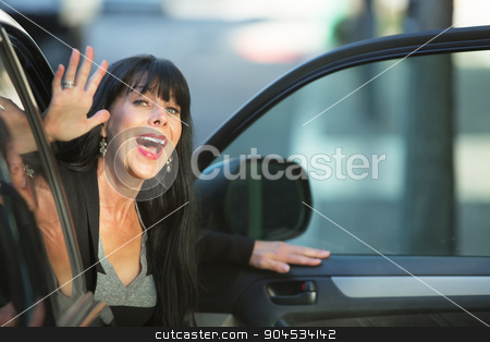 Attractive Woman Waving From Car stock photo, Attractive woman waving as she exits vehicle on downtown street by Scott Griessel