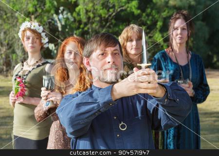 Bearded Pagan Priest with Athame stock photo, Bearded pagan priest with group and holding ritual knife by Scott Griessel