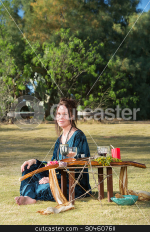Polytheist Woman at Altar stock photo, Beautiful polytheist woman in blue sitting outdoors by Scott Griessel