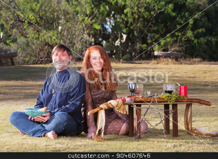 Happy Pagan Couple Outdoors stock photo, Happy pagan couple at altar with candles and goblets by Scott Griessel