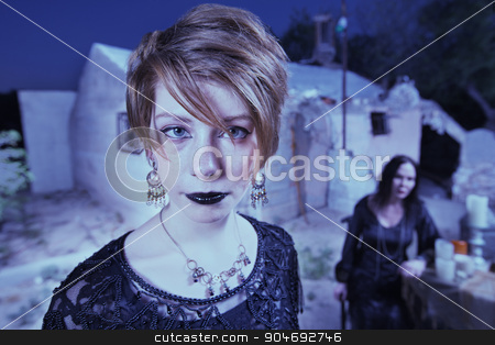 Pair of Witches Outdoors stock photo, Young woman in black outdoors with witch and altar by Scott Griessel
