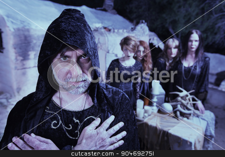 Occult Man with Women stock photo, Occult man in hood with group of women at temple by Scott Griessel