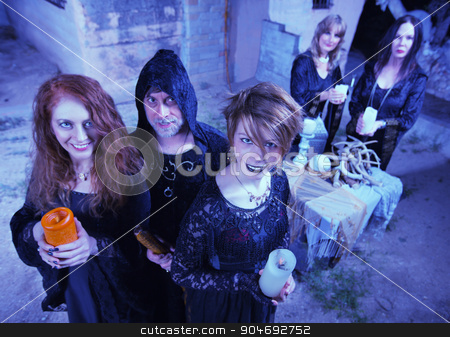 Coven of Smiling Witches stock photo, Coven of smiling witches outdoors holding candles by Scott Griessel