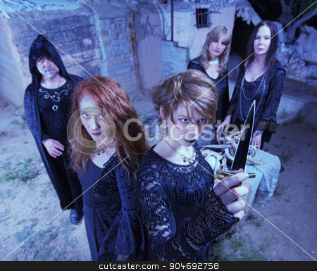 Occult Sacrifice Ritual stock photo, Five witches with dagger in occult sacrifice ritual by Scott Griessel