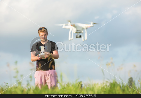 Man Controlling a Drone stock photo, Man outdoors with remote control and flying surveillance drone by Scott Griessel