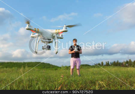 Person with Drone in Field stock photo, Person in field controlling drone with camera by Scott Griessel