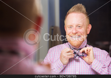 Man Tying Bow-tie stock photo, Happy European man with beard tying a bowtie by Scott Griessel