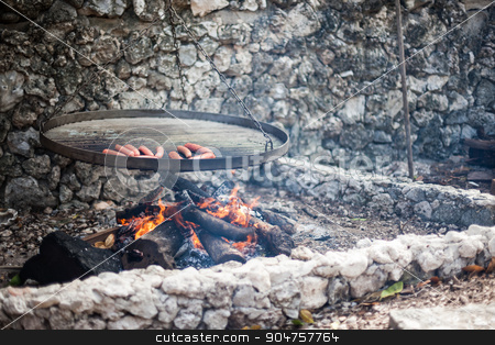 Sausages being grilled above a fire