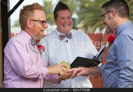 Spouse Puts Ring on Finger stock photo, Gay couple in wedding ring ceremony with minister by Scott Griessel
