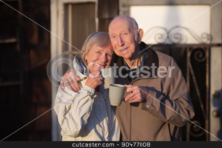 Happy Married Couple Outdoors stock photo, Happy married couple with cups standing outdoors by Scott Griessel