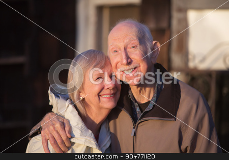 Grinning Older Couple stock photo, Grinning older couple embracing while standing outdoors by Scott Griessel