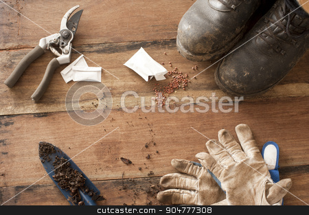 Gardening still life stock photo, Gardening still life with old boots, secateurs, trowel and gloves displayed in the corners on a rustic wood background by Stephen Gibson