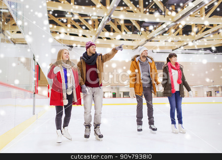 happy friends pointing finger on skating rink