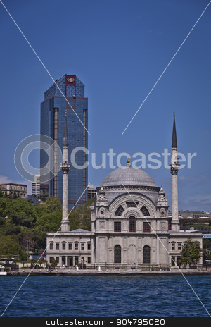 Dolmabahce Mosque on the Bosphorus in Istanbul stock photo, ISTANBUL, TURKEY – APRIL 27:  Traditional Dolmabahce Mosque on the Bosphorus in Istanbul with modern office building behind on April 27, 2012 in Istanbul, Turkey.  by Scott Griessel