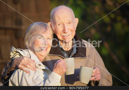 Older Couple with Coffee Outdoors stock photo, Older senior couple together outdoors holding coffee by Scott Griessel