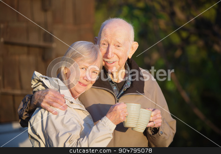 Husband and Wife with Mugs stock photo, Cute couple standing outdoors holding coffee mugs by Scott Griessel
