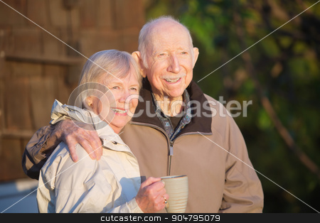 Cheerful Couple Outdoors stock photo, Cheerful couple standing outdoors with coffee mug by Scott Griessel
