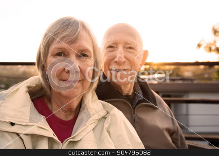 Grinning Couple in Jackets stock photo, Grinning Caucasian senior couple in jackets sitting outdoors by Scott Griessel