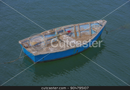 Bright Blue Rowboat stock photo, Colorful weathered rowboat anchored in shallow ocean water by Scott Griessel