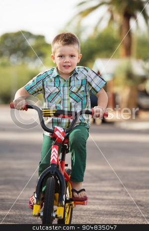 Cute Child On Bike stock photo, Cute child happily riding a bicycle on road by Scott Griessel