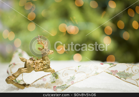 Christmas Reindeer Ornament, Ribbon on Snow with Tree and Lights stock photo, Decorative Christmas Reindeer Ornament and Ribbon on Snow with Tree and Lights Background. by Andy Dean