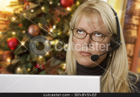 Upset Woman with Headset In Front of Christmas Tree and Computer stock photo, Upset Woman with Phone Headset In Front of Christmas Tree and Computer Screen. by Andy Dean