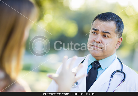 Hispanic Male Doctor or Nurse Talking With a Patient stock photo, Hispanic Male Doctor or Nurse Talking With a Patient Outdoors. by Andy Dean