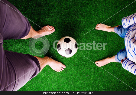 Father and son with soccer ball against green grass