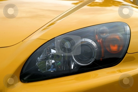 Headlight Of A Car stock photo, Head light of a yellow sports car by Henrik Lehnerer