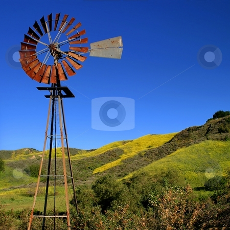 Windmill stock photo, Windmill with a green and yellow spring field in the background. by Henrik Lehnerer