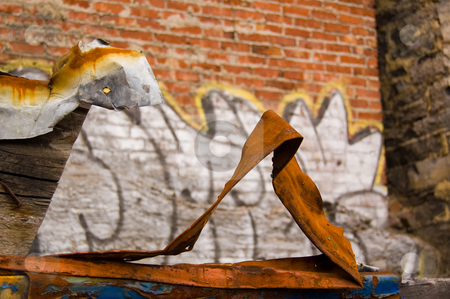 Rusty piece of metal stock photo, Old rusty pieces of iron in front of a graffiti covered wall by Jean Larue-Frechette