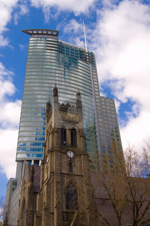 Modern And Old Architecture Contrast stock photo, An old church in front of a modern skyscraper in downtown montreal by Jean Larue-Frechette