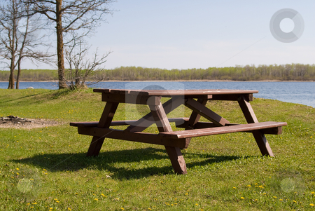 Picnic Table stock photo, A wooden picnic table placed near a small lake by Richard Nelson