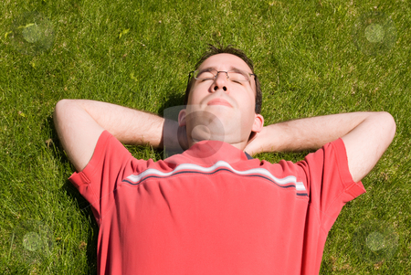 Man Relaxing In The Sun stock photo, A young man wearing glasses, lying on the grass, relaxing in the sun by Richard Nelson