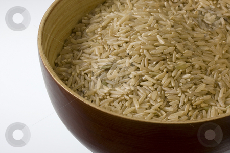 Long brown rice stock photo, A wooden bowl of long grained brown rice against white background by Marek Uliasz