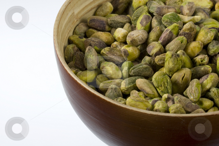 Shelled pistachio nuts stock photo, A wooden bowl of shelled pistachio nuts against white background by Marek Uliasz
