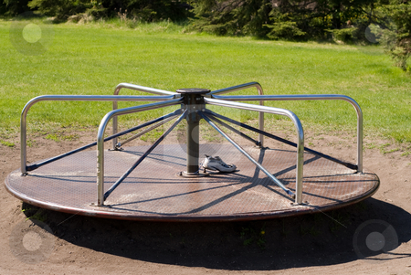 Playground Equipment stock photo, A playground merry-go-round in the grass by Richard Nelson