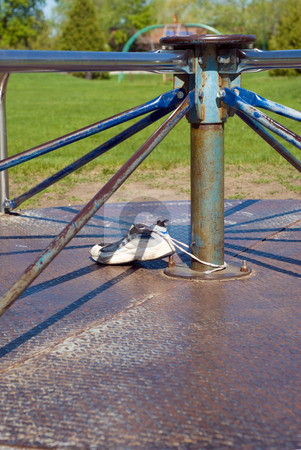 Merry-go-round stock photo, Close-up of a playground merry-go-round with an abandoned shoe on it by Richard Nelson