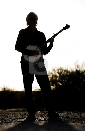 Banjo Player stock photo, Banjo player with his instrument in silhouette by Scott Griessel