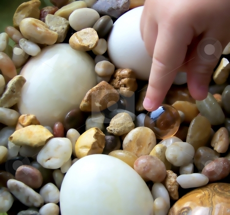 Young Child Reaching for Pebble, with Stone Eggs stock photo,  by Jill Oliver
