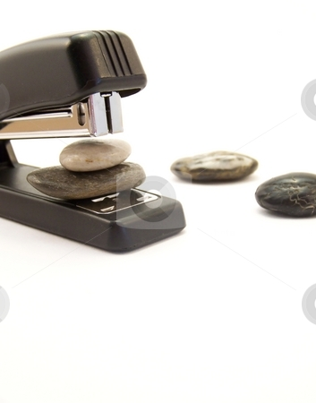 Super Stapler, Vertical stock photo, Image of a black stapler about to staple two stones together.  Other stones are nearby.  Vertical orientation. by Jill Oliver