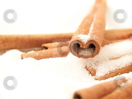 Cinnamon Sticks and Sugar stock photo, Horizontal image of a heart-shaped cinnamon stick in white granulated sugar, with other sticks visible. by Jill Oliver