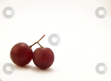 Red Grapes that look like Cherries, Horizontal stock photo, Image of two red grapes joined together, resembling cherries, placed in bottom lefthand corner of frame.  White background and horizontal orientation. by Jill Oliver