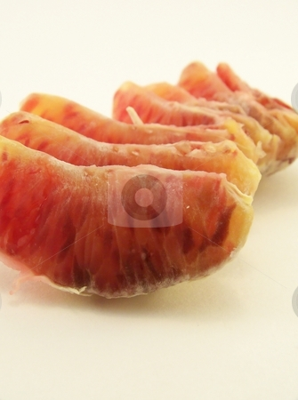 Blood Orange slices stock photo, Image of a peeled blood orange, segments lined up in a row.  Vertical orientation. by Jill Oliver