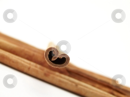 Cinnamon Sticks stock photo, Horizontal image of piled cinnamon sticks flowing from one side of the frame to the other, with a single stick placed on top.  Curves of the single stick resemble a heart. by Jill Oliver