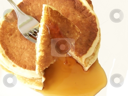 Pancakes 6 stock photo, Image of two sliced pancakes and metal fork, with a stream of maple syrup running off slices onto plate. by Jill Oliver