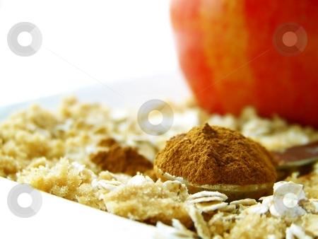 Cinnamon in Measuring Spoon stock photo, Image of a heaping spoonful of cinnamon, with brown sugar and oats surrounding and a bright red apple in the backgroujnd.  Room for text remains in top left hand quarter of the image.  Horizontal orientation. by Jill Oliver